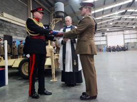 Commanding Officer handing over the lowered flag